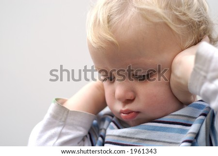 young boy covering ears - stock photo