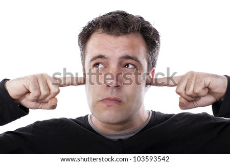 young boy covering his ears with his fingers and grimacing, ignoring what you are saying. - stock photo