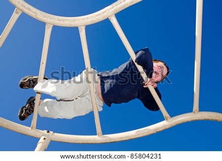 Young boy crawling over monkey bars on playground - stock photo