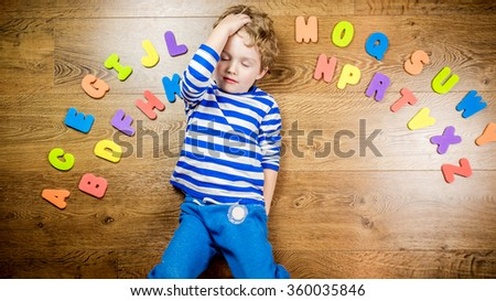young boy demonstrating his collection of capital letters with thoughtful face while laying on brown wooden floor - stock photo