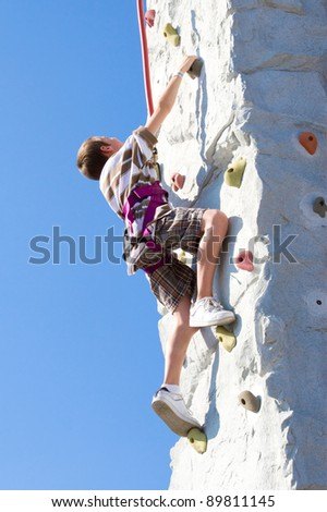 Young boy determination while climbing up an artificial rock wall