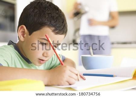 Young boy doing his homework - stock photo