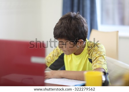 Young boy doing his homework on a computer - shallow depth of field - stock photo