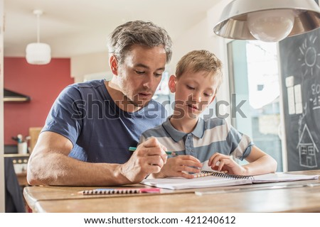 Young boy doing his school homework with his father, at home, he is writing in his notebook, Dad and his son are concentrated on the problem - stock photo