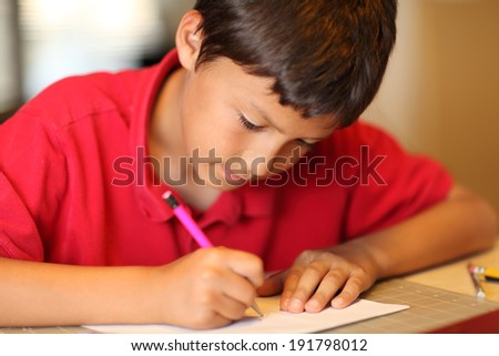 Young boy drawing for homework - with very shallow depth of field - stock photo