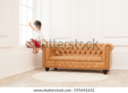 Young boy drawing on glass with finger while sitting on window sill at home  - stock photo