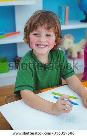 Young boy drawing on paper at their desk - stock photo