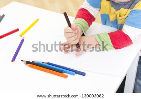 Young boy draws around his hand - stock photo