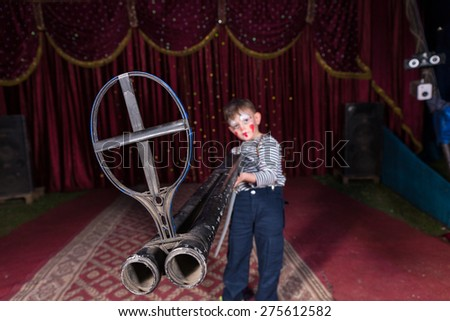 Young Boy Dressed as Clown Holding Large Double Barreled Shot Gun on Stage with Red Curtain - stock photo
