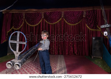 Young Boy Dressed as Clown Standing on Stage Holding Large Double Barreled Shot Gun with Iron Sight, Perspective Exaggerates Gun Size - stock photo