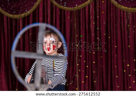 Young Boy Dressed as Clown Wearing Make Up and Striped Shirt Looking Serious and Framed in Iron Gun Sight and Standing on Stage with Red Curtain - stock photo