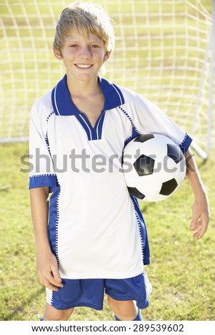 Young Boy Dressed In Soccer Kit Standing By Goal - stock photo