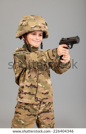 Young boy dressed like a soldier with a gun isolated on gray background - stock photo