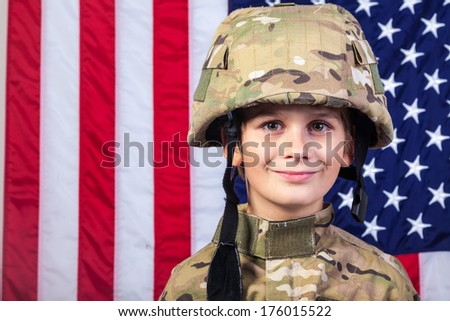 Young boy dressed like a soldier with American flag in background.