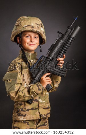 Young boy dressed like a soldier with rifle isolated on black background - stock photo