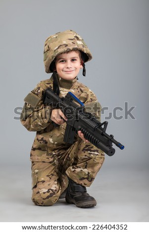 Young boy dressed like a soldier with rifle isolated on gray background - stock photo