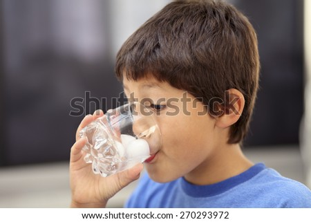 Young boy drinking a glass of cold water with ice - shallow depth of field - stock photo