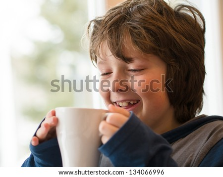 Young boy drinking a hot chocolate - stock photo