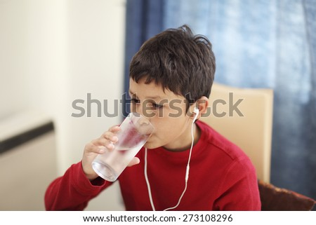 Young boy drinking from a glass of water while watching the computer - with shallow depth of field - stock photo