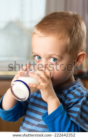 Young boy drinking milk out of glass in the kitchen - stock photo