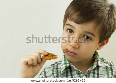Young boy eat chicken finger - stock photo