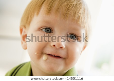 Young boy eating baby food with mess on face - stock photo