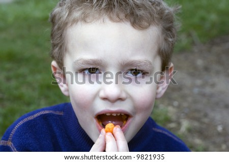 Young boy eating cheese orange snack - stock photo