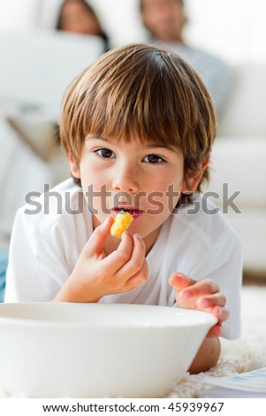 Young boy eating chips lying on the floor in the living-room - stock photo