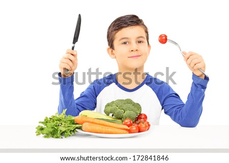 Young boy eating vegetables seated at table isolated on white background - stock photo