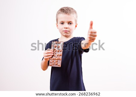 Young boy eats chocolate tablet - stock photo