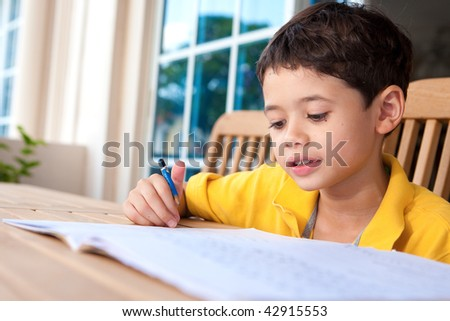 Young boy engross in his homework in an outdoor setting