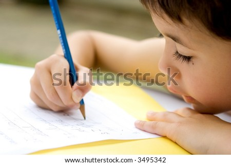 Young boy enjoying his his writing as part of homework, outdoors. - stock photo