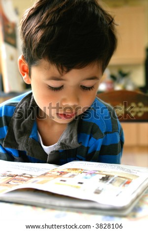 Young boy enjoying his reading book, indoor setting.