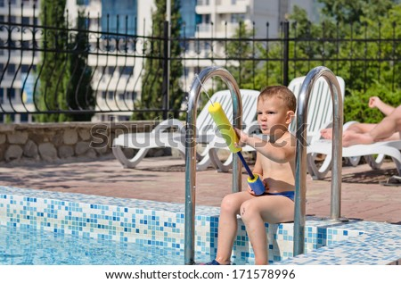 Young boy enjoying the summer sun playing in a swimming pool sitting on the steps in his costume holding a colourful plastic toy with adults visible on loungers behind him - stock photo
