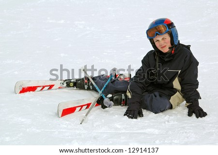 young boy fallen in the snow - stock photo