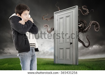 Young boy fearing a monster behind a door - stock photo