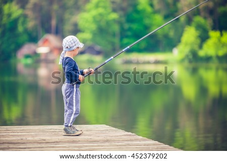 Young boy fishing from wooden dock