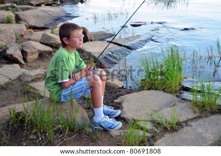Young boy fishing in a forest lake