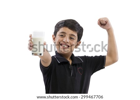 Young boy flexing his arm while holding a glass of milk - stock photo