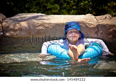 Young boy floating in a inner tube  eyes closed in a blissful state - stock photo