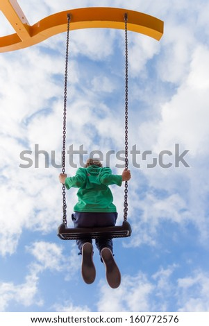 Young boy flying high on a swing against a blue sky with white clouds - stock photo
