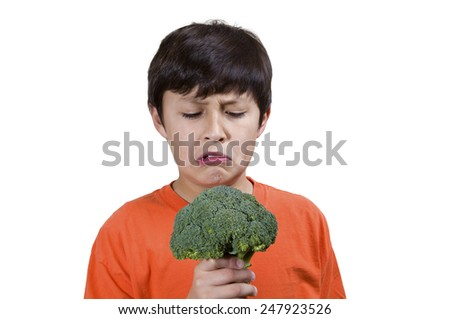 Young boy frowns while holding broccoli on white background - stock photo
