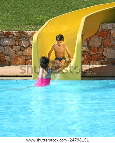 Young boy getting help from his sister as he slid down the water slide at swimming pool - stock photo