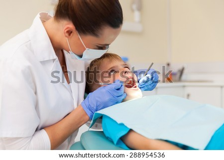 young boy getting his teeth examined in clinic