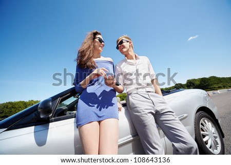Young boy gives his girlfriend keys from the cabriolet, both smile - stock photo