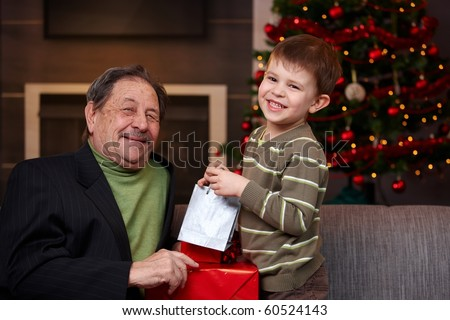 Young boy giving christmas present to happy grandfather, smiling. ? - stock photo