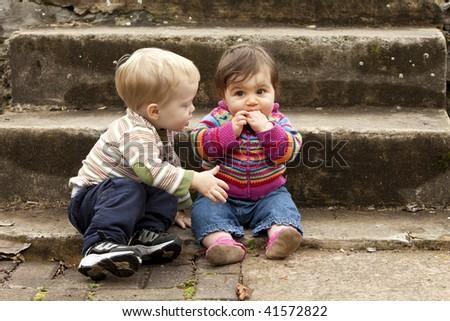 Young Boy Giving Sad Baby Girl a Hug - stock photo