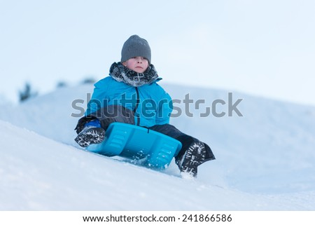 Young boy gliding downhill on a blue sledge - stock photo