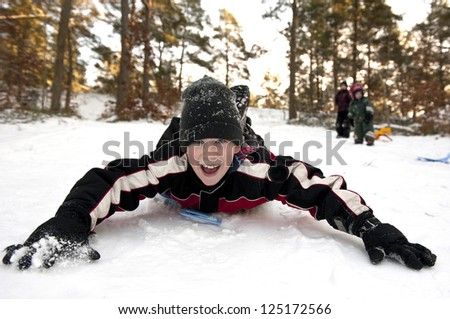 Young boy gliding on his belly in the snow - stock photo