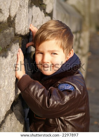 young boy grinning leaning on brick wall - stock photo